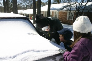 "My husband, Dwight, doing a ""faceprint"" in the snow, while the grandkids watch."