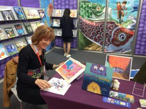 Illustrator Leslie Helakoski doing an art demo and book showcase in the SCBWI booth at the Bologna Book Fair